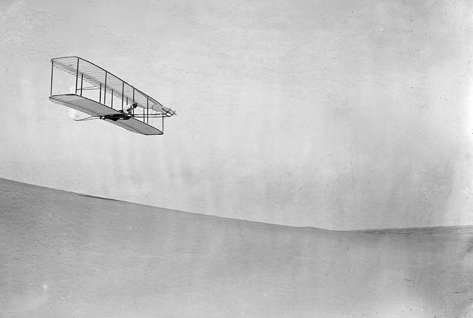 Wilbur Wright pilots a full-size glider down the steep slope of Big Kill Devil Hill in Kitty Hawk, North Carolina, on October 10, 1902. This model was the third iteration of the Wright brothers' early gliders, equipped with wings that would warp to steer, a rear vertical rudder, and a forward elevator.