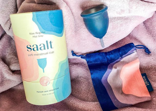 Saalt soft menstrual cup packaging in mist grey next to the storage bag