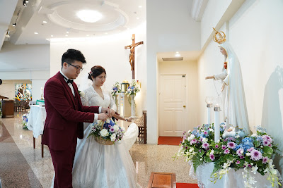 bride and groom offering flowers to mother mary