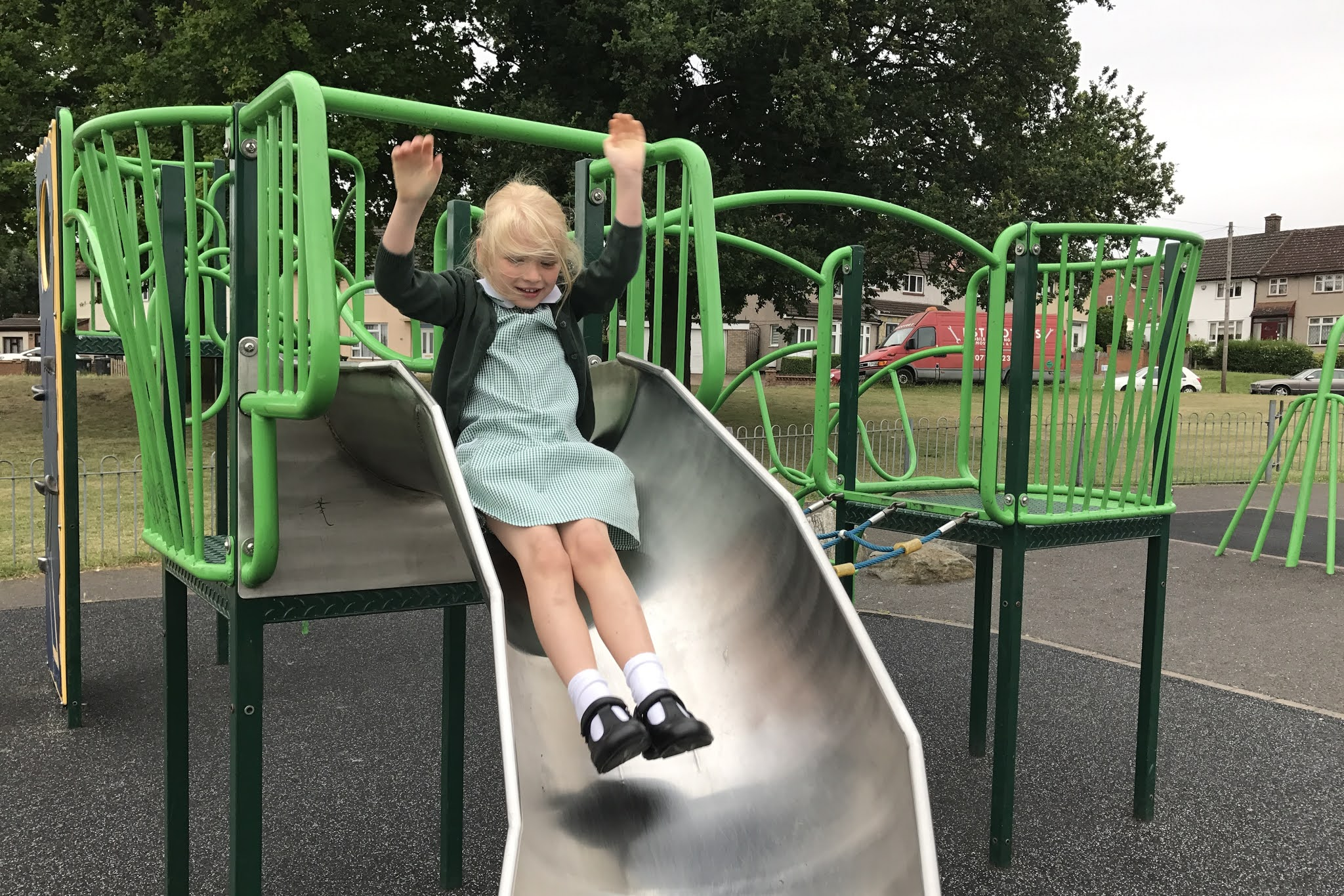 A climbing frame in a loughton playground with a girl going down a slide in school uniform