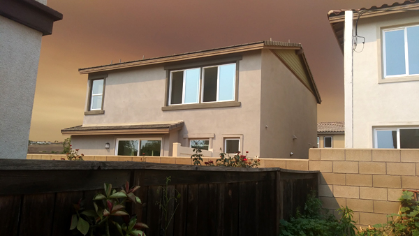 The smoke cloud from the Bobcat Fire lurks above a recently-built 2-story home behind my backyard in Pomona, California...on September 9, 2020.
