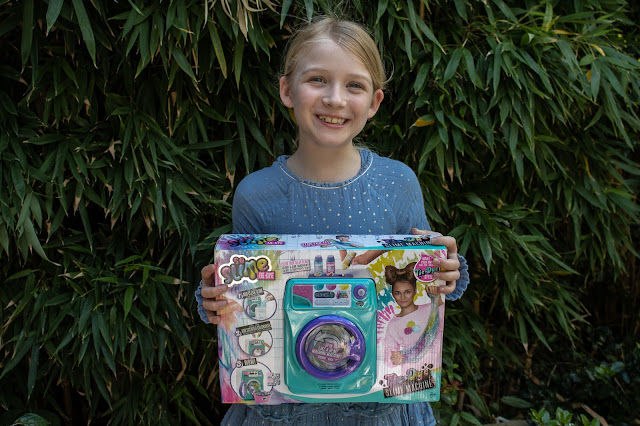 A girl holding the So Slime Tie-Dye Slime Machine box happy to be reviewing it
