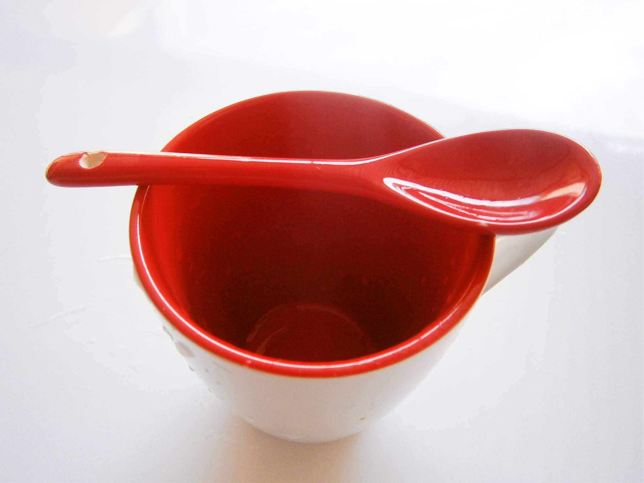 Descripción de la fotografía. Taza decorativa de color rojo que sirve para fiestas o eventos sociales. Taza de color roja para celebrar la navidad y puesta sobre un fondo de color blanco.