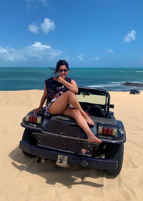 mulher jovem de oculos escuros e roupa de praia sentada em cima de um buggy azul estacionado em dunas de areia dourada