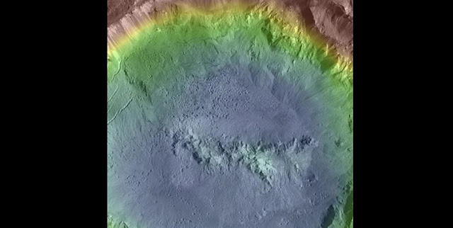 Image of Haulani Crater, Ceres, showing abundant pitted materials on the crater floor. Similar pitted materials have previously been identified on Mars and Vesta, and are associated with rapid volatile release following impact. Their discovery on Ceres indicates pitted materials may be a common morphological indicator of volatile-rich materials in the asteroid belt. Haulani Crater is 34 km in diameter. Color indicates topography.  Credit: NASA/MPS/PSI/Thomas Platz