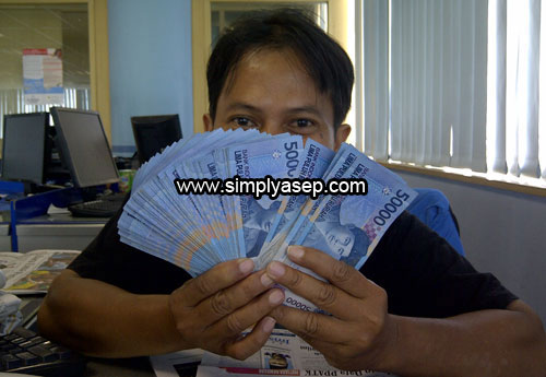 MONEY : I holded up some Indonesian money in my hand about 5,000.000 rupiahs in small 50 thousands note for each.  Foto Kekes