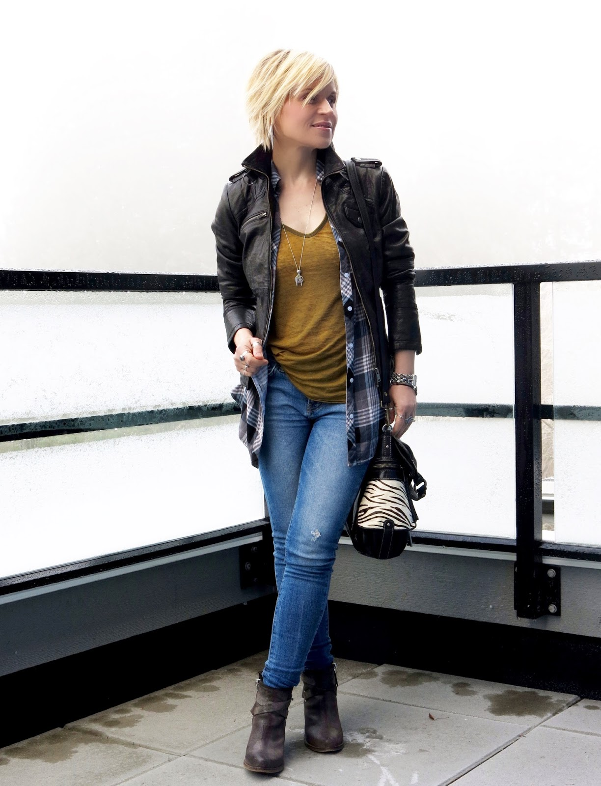 styling a moto jacket with layered shirts, skinny jeans, and booties