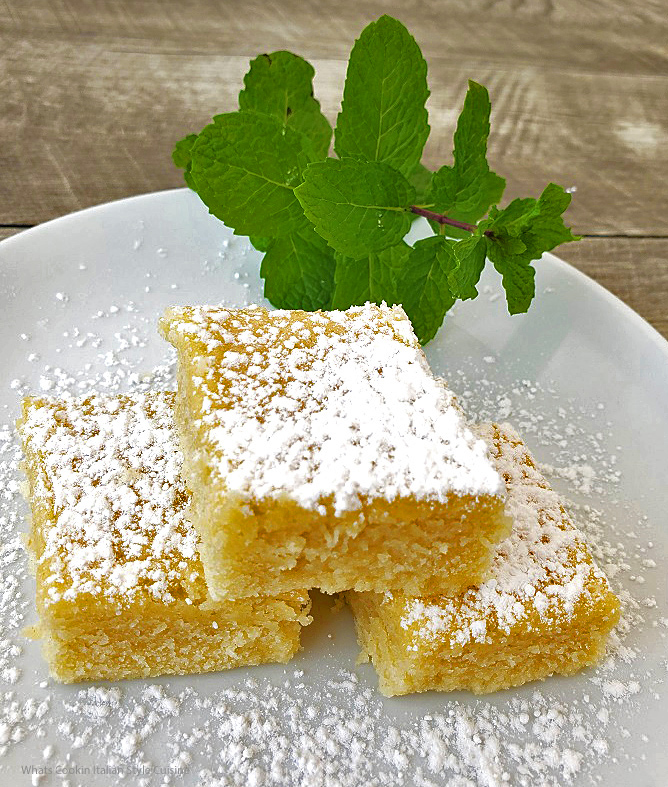this is three square pieces of hot milk cake on a plate sprinkled with powdered sugar they are on a white plate with mint in the back on a grey board.