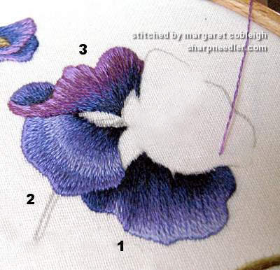 Pointing out problem areas on thread painted pansies (Pansies designed by Trish Burr)