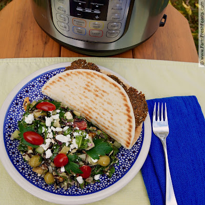 pic of an Instant Pot on a table with a plate of Greek Wild Rice Salad and a falafel-stuffed pita