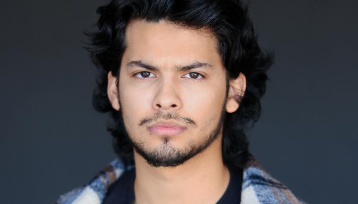 Imagem: o ator Xolo Maridueña, um jovem latino de uns vinte anos, com cabelos pretos longos, barba curta crescendo, rosto redondo, em um casaco quadriculado em tons de branco, azul e marrom e um fundo cinza-claro.