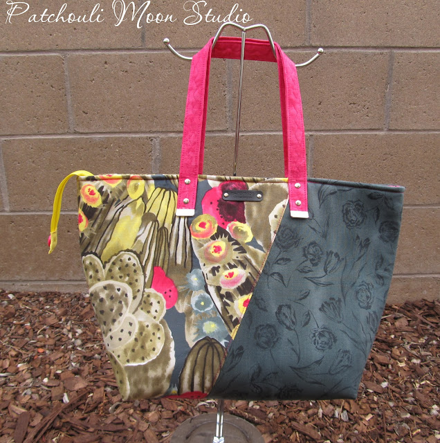 Large tote bag in cactus print and dark fabric sewn on an angle with yellow zipper