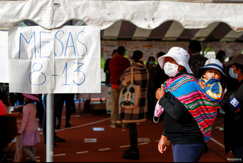 Una mujer con un niño acude a votar en las elecciones regionales de Bolivia el 7 de marzo de 2021 / REUTERS