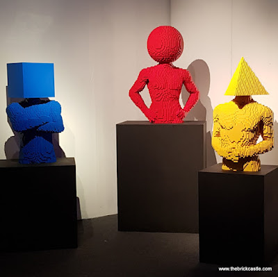 trio of humans with shapes for heads blue square, red ball, yellow triangle