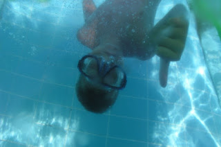 Picture of a boy, upside down in the pool and wearing Goggles, giving the camera a thumbs up. Cameras in The Pool Area & Swimming Lessons