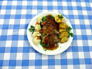karkówka pieczona - plastry podane na talerzu z ziemniakami i kalafiorem