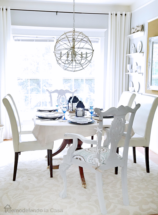 dining room with sphere chandelier and coastal tablescape