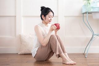 足が寒いので暖かい飲み物を飲んでいる女性