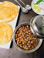 Serving two bhature with chole and onion slices, lemon wedges,green chili, spoon and fork in background