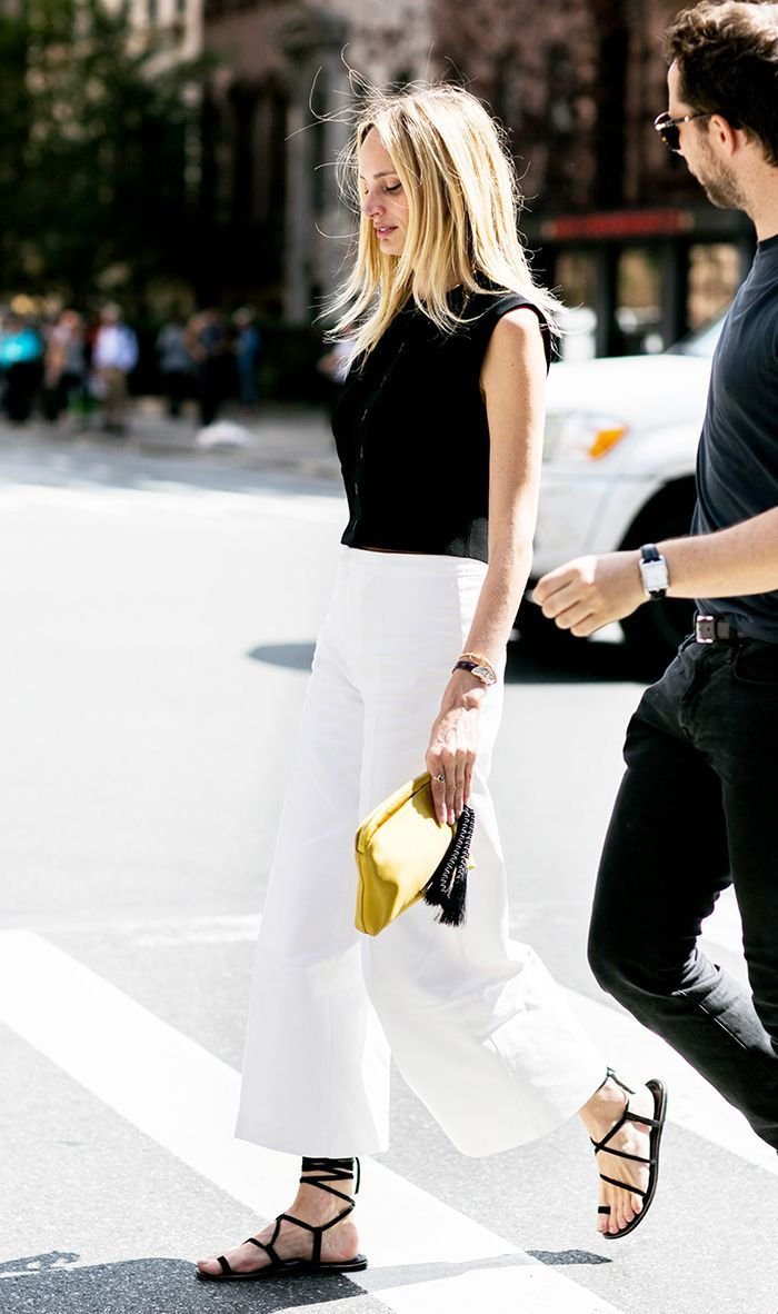 Black and White Summer Outfit Idea - Lauren Santo Domingo street style look with a sleeveless black top, cropped wide-leg white jeans, and strappy flat black sandals