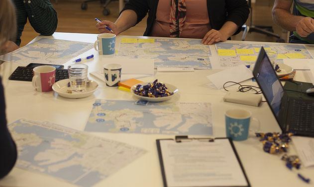 Pöydällä karttoja, muistiinpanovälineitä, kahvikuppeja, tietokone ja näkyy neljän henkilön kädet.