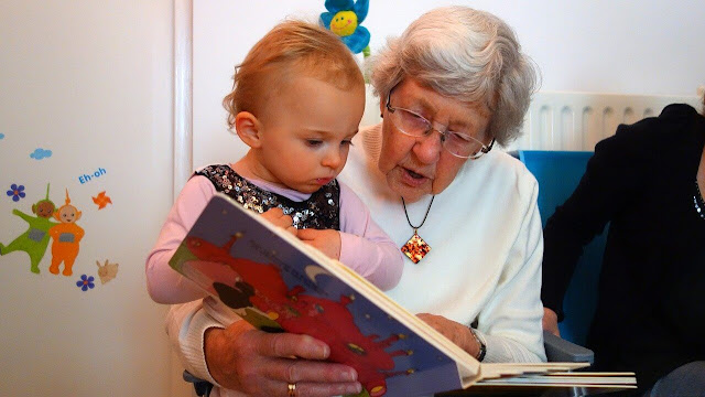 Niña de menos de dos años con la abuela sosteniendo libro y leyendo