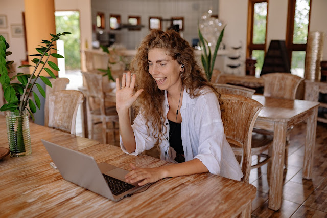 A happy woman taking a call on her laptop.