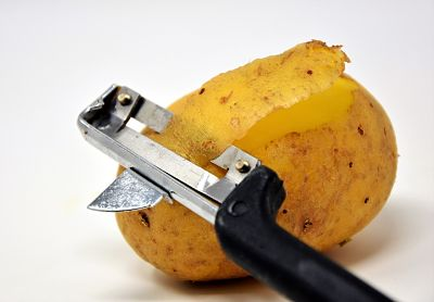 Papa entera. Pelapapas pelando una patata
