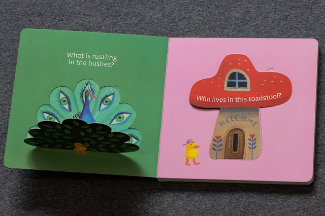 Sample pages from lift up the flap board book with a peacock hidden in a bush and puss in boots behind a toadstall