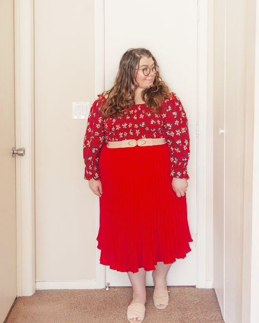 An outfit consisting of a red with a navy outlined white floral print off the shoulder with long ruffled sleeves dress tucked into a red pleated midi skirt, belted with a pink belt and pink slide sandals.