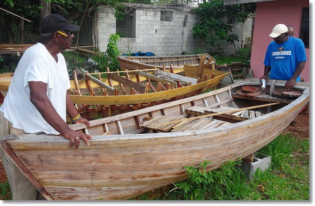 Two men and the wooden boat they built.