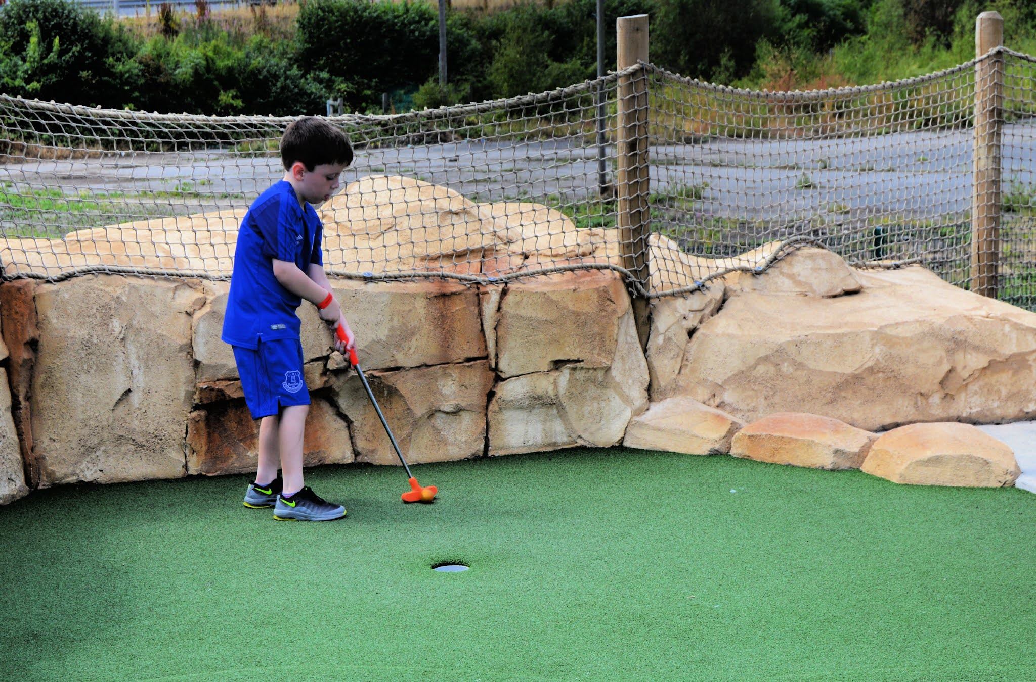 boy playing mini golf