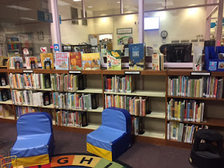 Two blue chairs sitting in front of shelf of picture books