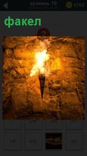 В стене в пещере висит горящий факел, Освещая все мрачное подземное помещение