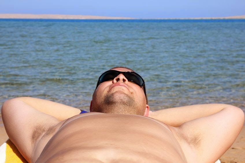 man sunbathing on a beach