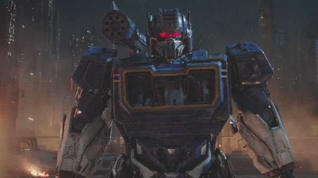 transformers autobots optimus prime blue metal truck silver arms staring in front of the large devastated buildings