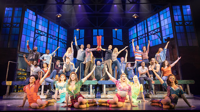 the factory worker cast of Kinky Boots stand on a conveyor belt, while the drag queen Angels sit on the floor downstage. Everybody is smiling and has their arms raised, they are celebrating.