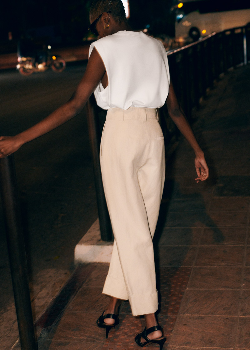 minimalist summer going out outfit idea white padded-shoulder top, high waisted tan pants, black strappy sandals