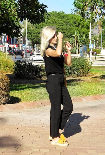 Alejandra Colomera con camiseta negra, pantalón formal negro, lazo en el cuello negro con lunares blancos y complementos mostaza