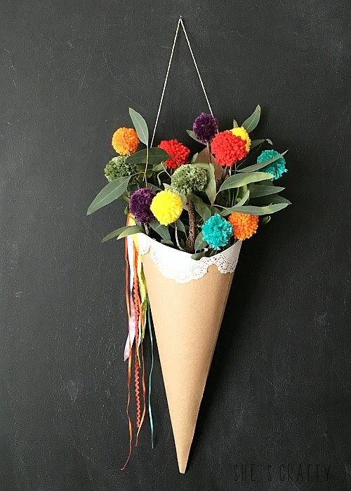 Make rainbow pom pom in a paper cone holder to freshen space for Spring