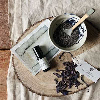 A flat lay of seeds and a ceramic spoon in a bowl on a wooden board with dark coloured dried leaves beside