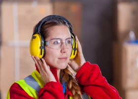 A woman wearing a protective hearing equipment.