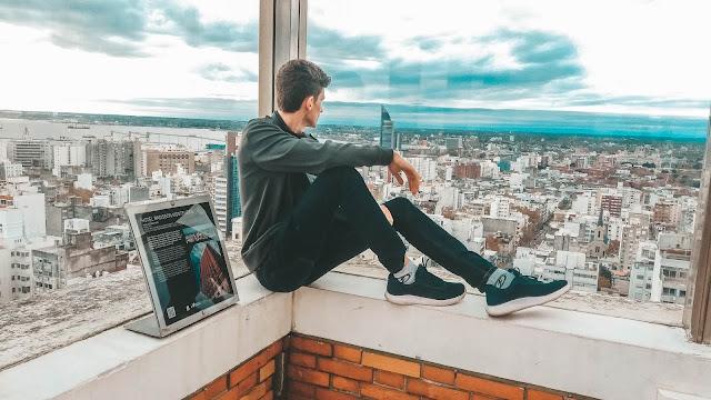 Menino sentado no muro, olhando para a cidade