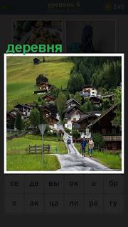 небольшая деревня в низине, дорога к ней и идут по ней люди