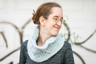 A woman wearing a blue bulky knit cowl. The cowl has a lace and cable pattern.