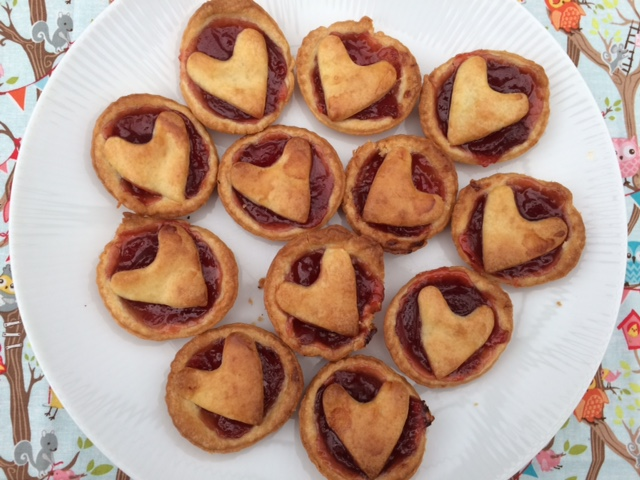 A plate full of jam tarts with heart tops