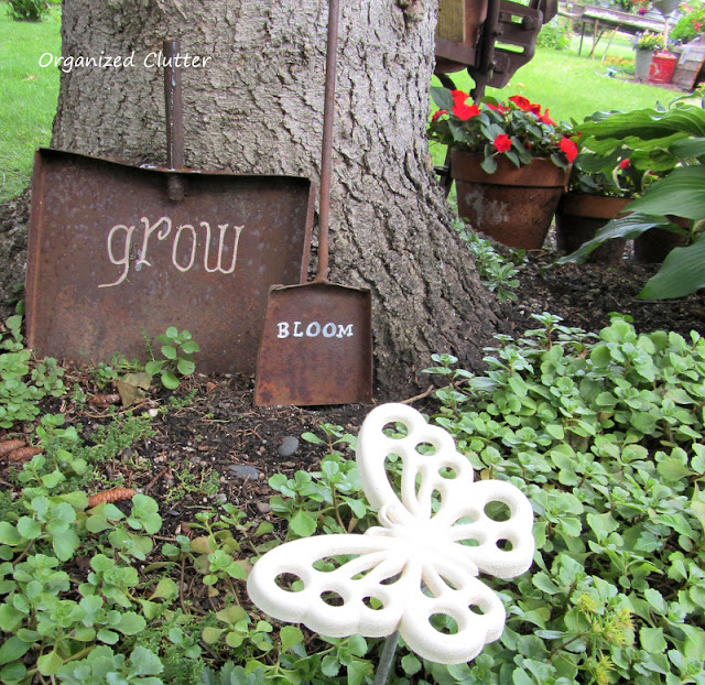 Photo of a rusty shovel head with a chalk transfer method garden word.
