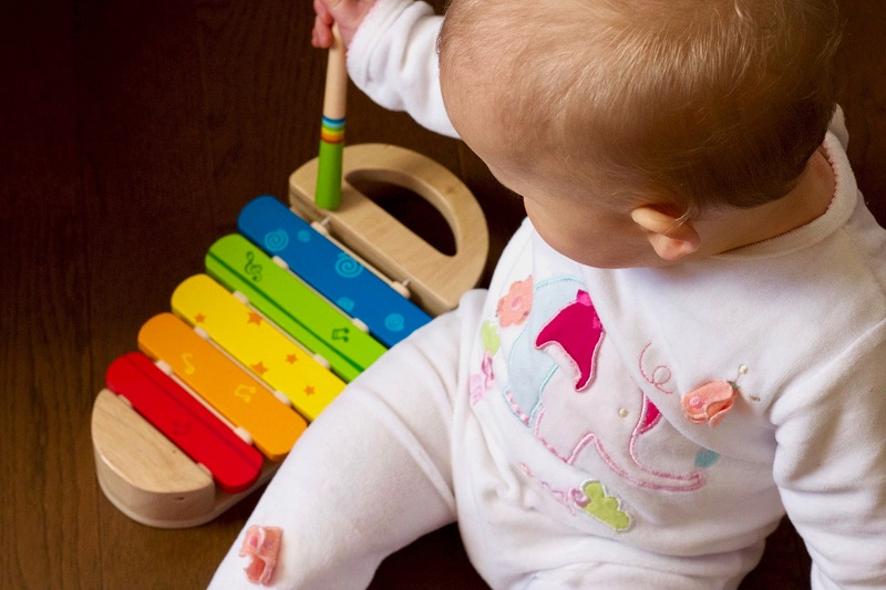 baby playing wooden xylophone