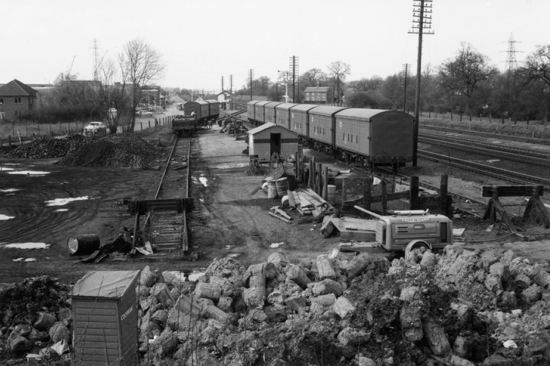 Photograph of Four wheeled wagon and vans supplying coal and products for the Kelloggs warehouse at Marshmoor sidings, January 1972