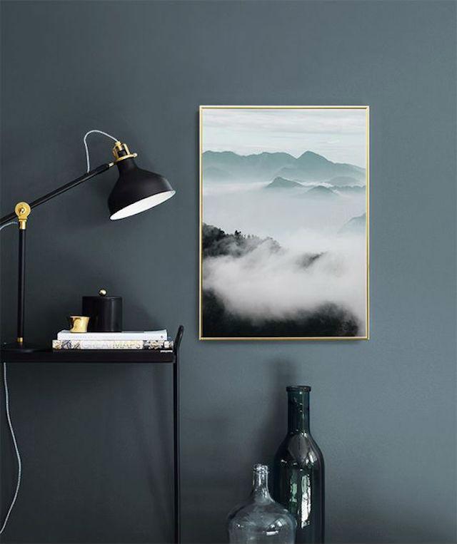 Pared pintada de oscuro con marco de fotos en color dorado y fotografía en blanco y negro
